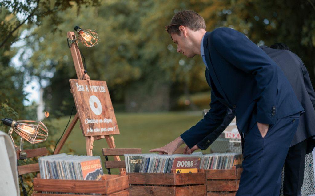 Personne regardant des disques d'un bar à vinyles durant un cocktail de mariage.